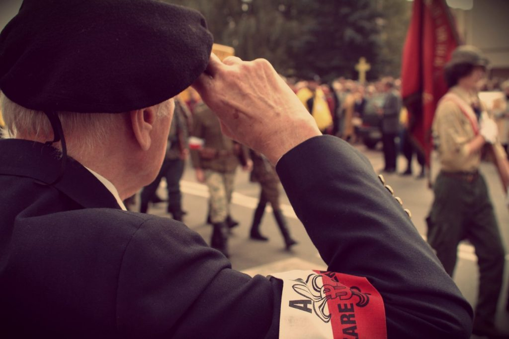 Obchody 60. rocznicy Powstania Warszawskiego we Włochach. Widok na salutującego Powstańca z opaską AK na ramieniu