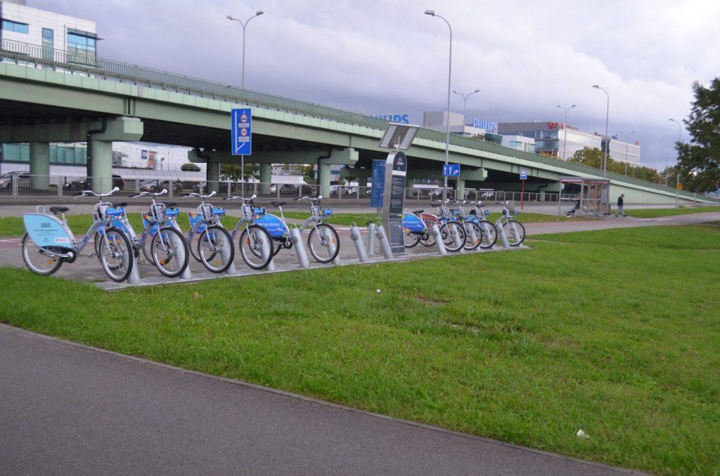 Rowery ustawione na stacji Veturilo u zbiegu ul. Popularnej i Al. Jerozolimskich. W tle estakada i fragment biurowca.