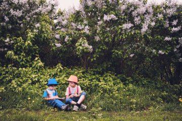 Dwójka dzieci siedząca na trawie w otoczeniu krzewów