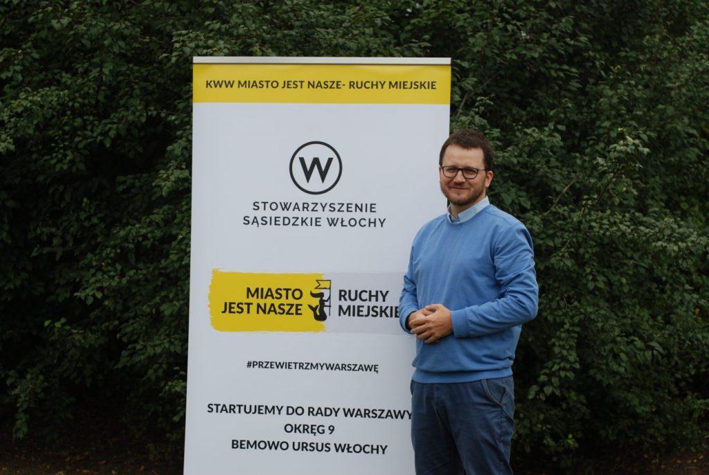 Przemysław Gan obok roll up z logo SSW i MJN Ruchy Miejskie