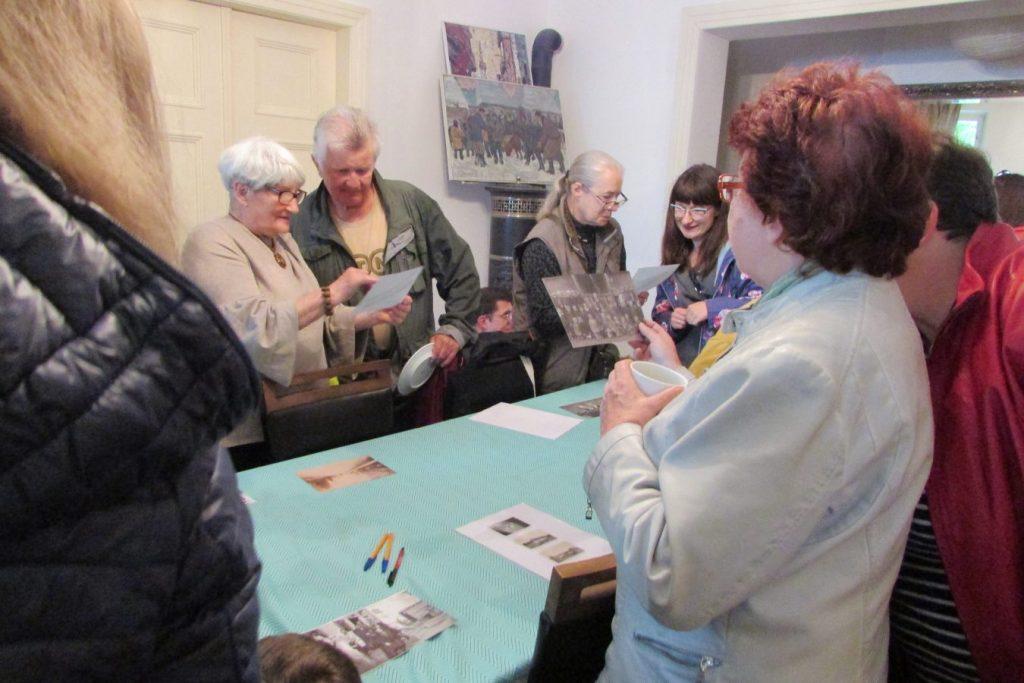 Sąsiedzkie Śniadanie w Porayowym Dworku - mieszkańcy ogladają stare zdjęcia na stole