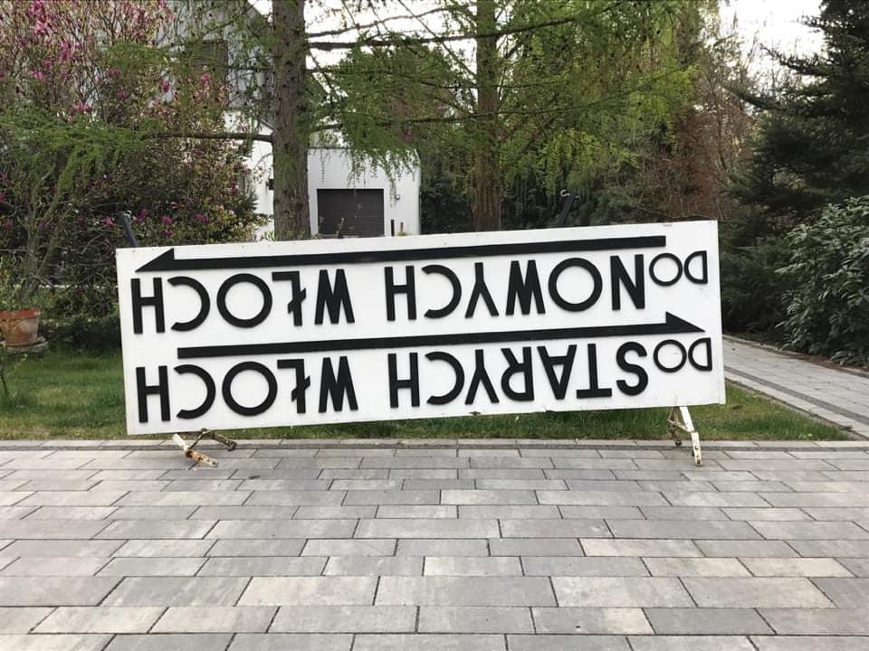 """Tablica kierunkowa """"Do Starych Włoch Do Nowych Włoch"""" stojąca na chodniku"""