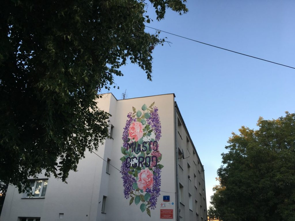 Widok na fasadę budynku i mural z napisem Miasto Ogród