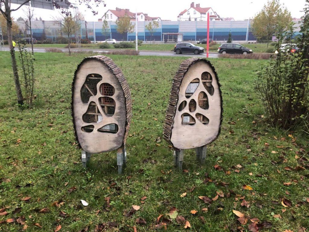 dwa drewniane hotele dla owadów stojące na trawniku
