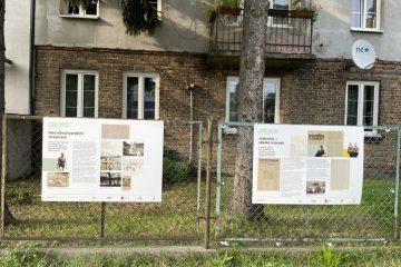 widok na dwie plansze wiszące na ogrodzeniu jako część wystawy Dawne Miasto Ogród Włochy na fotografii